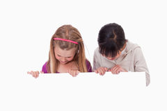 Girls looking at a blank panel Royalty Free Stock Image