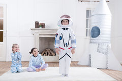 Girls looking on boy in astronaut costume stock images