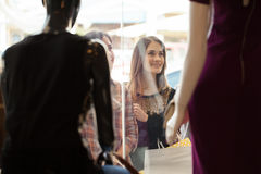 Girls looking at a clothing store display. Beautiful women and her friends looking at some mannequins on a window display at a shopping mall Stock Photography