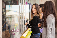Girls looking at a clothing store display. Cute young brunette and her friends doing some shopping and standing outside a clothing store Stock Images