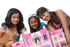 Girls looking into a dollhouse Stock Photos