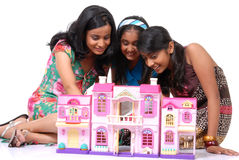 Girls looking into a dollhouse. Group of three girls looking into doll house Royalty Free Stock Photo