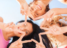 Girls looking down and showing finger five gesture Royalty Free Stock Image