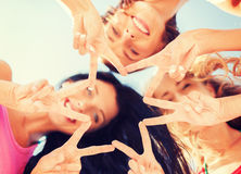 Girls looking down and showing finger five gesture Stock Photo