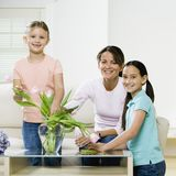 Girls looking at flowers. Two girls and mother with flowers on table Stock Photos