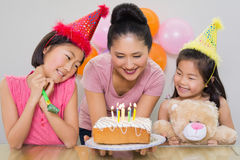 Girls looking at mother with cake at a birthday party Royalty Free Stock Photography