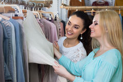 Girls looking for new garments. Two girls looking for new garments at the store royalty free stock image