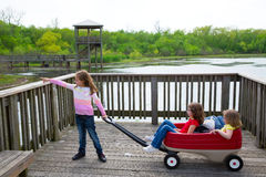 Girls looking at park lake with outdoor dump cart Royalty Free Stock Photos