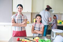 Girls are looking and posing on camera. They keep their hands crossed. Girls have a rest. Dad and son work together. Behind. They cook royalty free stock photo