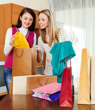 Girls looking purchases from shopping bags Royalty Free Stock Photo