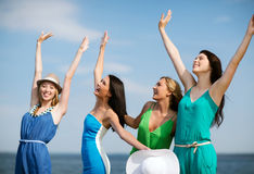Girls looking at the sea with hands up Stock Photo