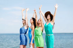 Girls looking at the sea with hands up Royalty Free Stock Photography