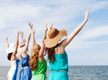 Girls looking at the sea with hands up Stock Images