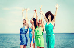 Girls looking at the sea with hands up Stock Photos