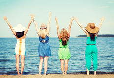 Girls looking at the sea with hands up Royalty Free Stock Photo