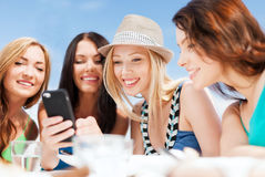Girls looking at smartphone in cafe on the beach Royalty Free Stock Photos