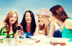 Girls looking at smartphone in cafe on the beach Royalty Free Stock Photography