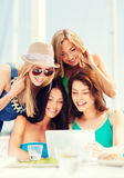 Girls looking at tablet pc in cafe Royalty Free Stock Photos