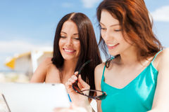 Girls looking at tablet pc in cafe Royalty Free Stock Images