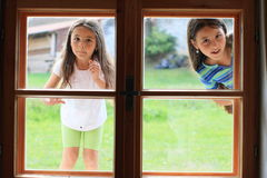 Girls looking into window. Two little girls looking into wooden window Stock Images