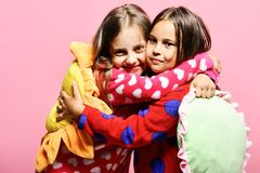 Girls with loose hair hug. Kids with smiling faces. Girls with loose hair hug each other. Kids with smiling faces hold green and yellow sun pillows. Friends in stock images
