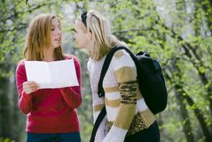 Girls lost in forest. Two girls lost in the woods who are checking a map Royalty Free Stock Photography