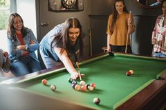 Girls Love Pool Too. Small group of female friends playing a game of pool in a games room in a house royalty free stock photography
