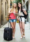 Girls with luggage and map Royalty Free Stock Photo
