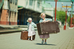 Girls with luggage at the railway station Royalty Free Stock Photography