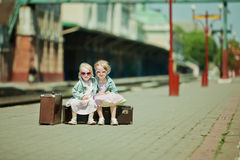 Girls with luggage at the railway station Stock Image