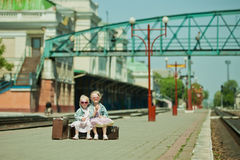 Girls with luggage at the railway station Stock Photo