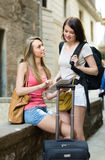 Girls with luggage reading map Royalty Free Stock Photo