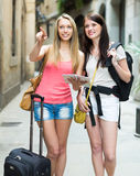 Girls with luggage reading map Royalty Free Stock Photography