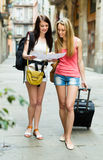 Girls with luggage reading map Stock Photo