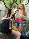 Girls with luggage reading map Stock Image