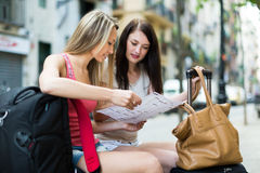 Girls with luggage reading map Stock Images