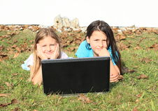 Girls lying behind a notebook Stock Photo