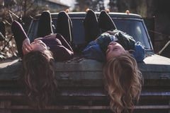Girls lying on bonnet of four by four