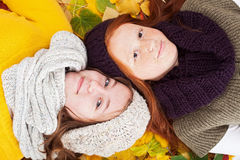 Girls lying in  leaves. Smiling girls portrait, lying in autumn leaves Royalty Free Stock Photos