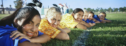 Girls Lying In Row On Soccer Field Royalty Free Stock Images