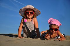 Girls lying on the sandy beach. Friends Stock Images