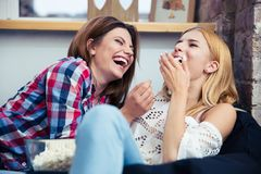 Girls lying on the sofa and eating popcorn Royalty Free Stock Photography