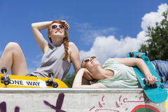 Girls lying on a vert ramp with skateboards stock photography