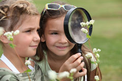 Girls with magnifying glasses Royalty Free Stock Photography