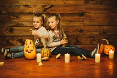 Two girls preparing for the holiday. Night, candles, pumpkin, tales. Girls make lamps out of pumpkins for Halloween stock images
