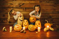 Two girls preparing for the holiday. Night, candles, pumpkin, tales. Girls make lamps out of pumpkins for Halloween Royalty Free Stock Photo