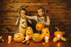Two girls preparing for the holiday. Night, candles, pumpkin, tales. Girls make lamps out of pumpkins for Halloween royalty free stock photography