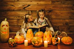 Two girls preparing for the holiday. Night, candles, pumpkin, tales. stock images