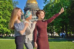 Girls make selfie on a phone on the background of St. Isaac`s Ca Royalty Free Stock Photography