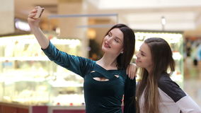 Girls make selfie on a phone at the Mall. Young girls make selfie on a phone at the Mall on a bright background stock video